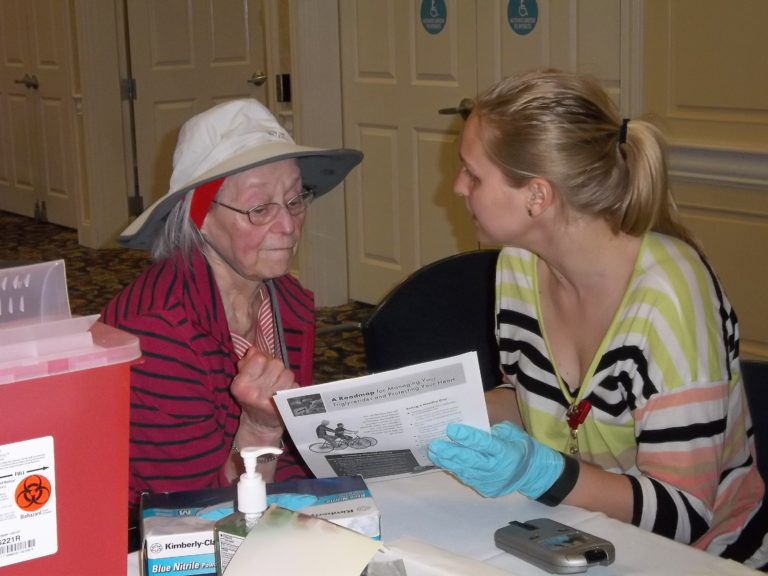 Nursing student providing health information to older adult