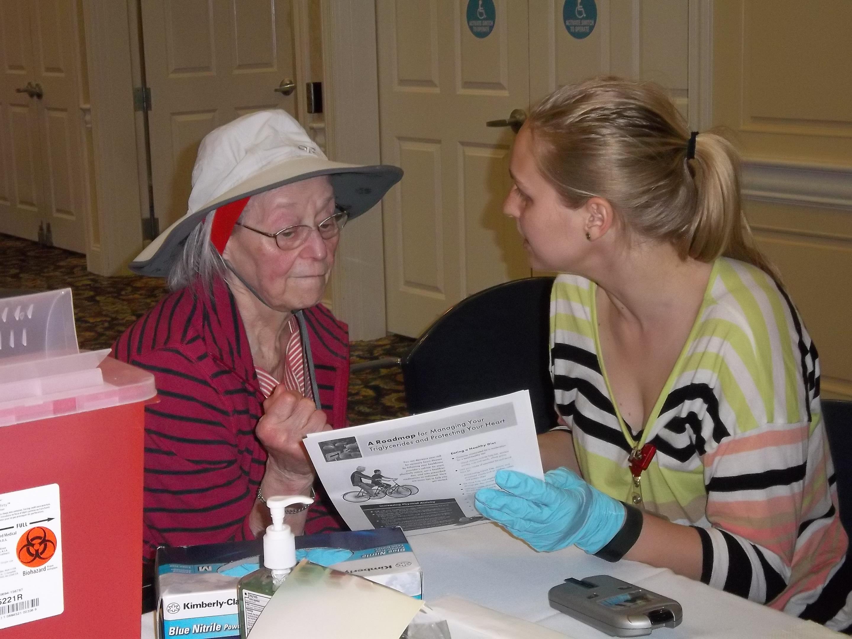 Nursing student providing health information to older adult